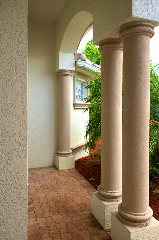Hardscape Design, Brick sidewalk using interlocking pavers with Arch and Columns on exterior of home in florida