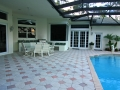 Swimming pool deck with paver tiles, brick pool coping and pool enclosure for custom pool