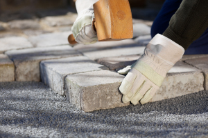 Close up shot of construction worker fixing a brick road