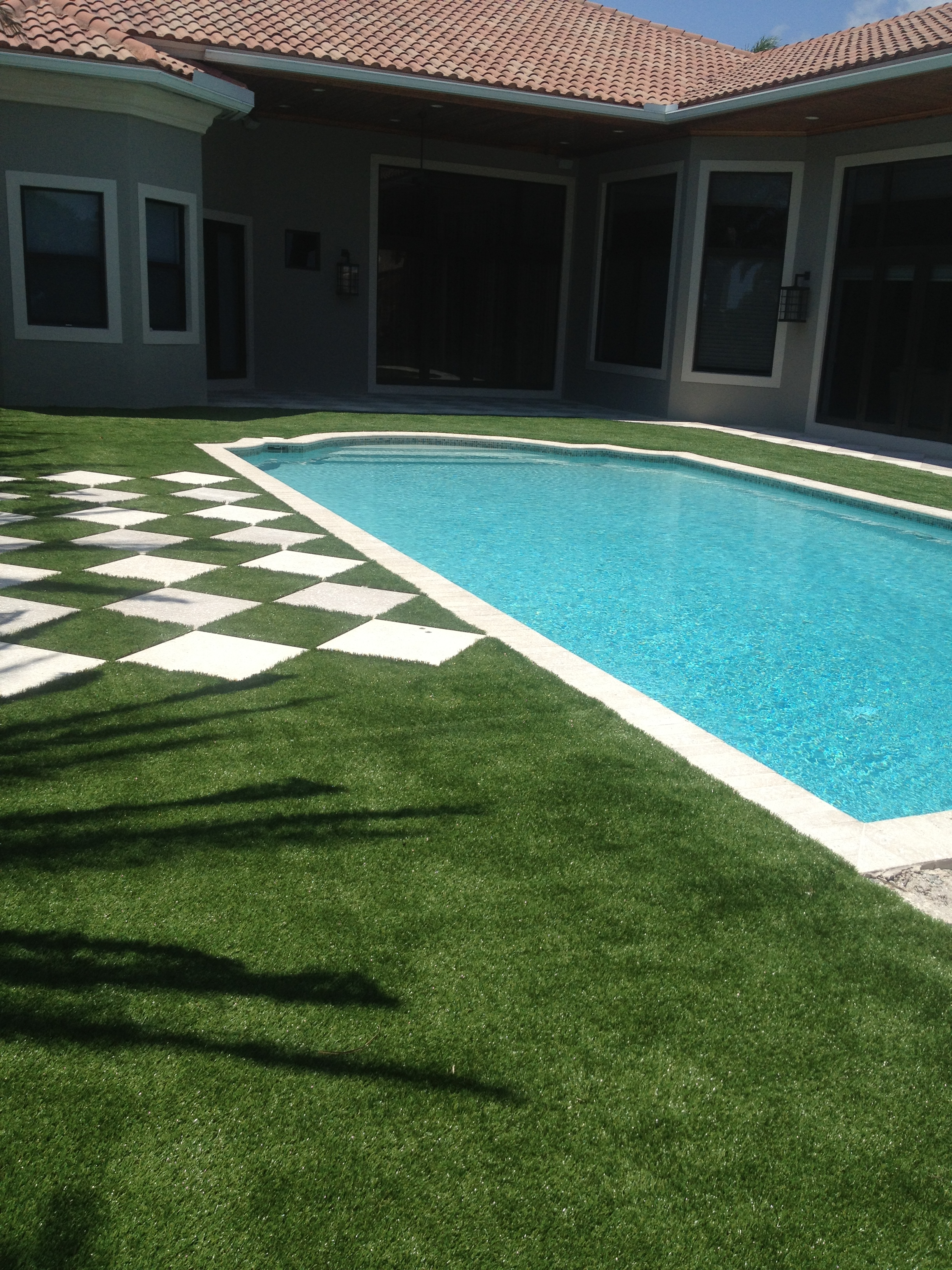 A pattern of pavers as a walkway in the grass alongside the pool