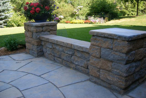 The back patio is designed with pavers and a retaining wall that also provides seating | America Pavers