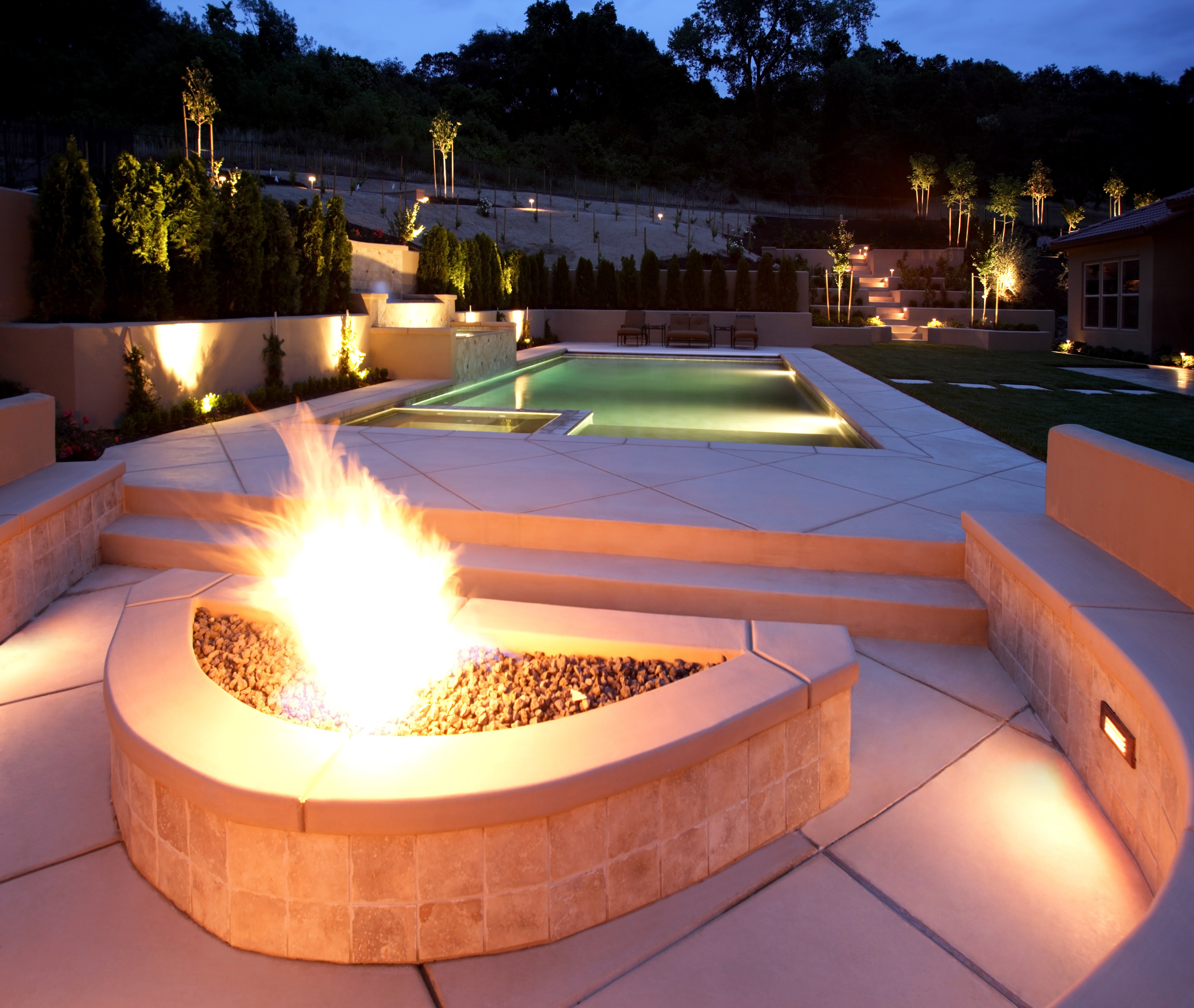 Combining pavers, bricks and tiles to create a poo and fire pit are with beauty and functional seating